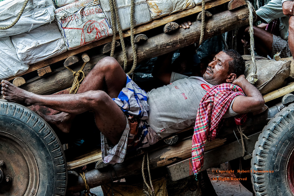 Indian Siesta: A tired labourer takes a well deserved mid day siesta on the cart he has just loaded, Kolkata (Calcutta) India.