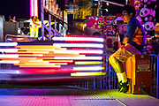 WASHINGTON, USA - September 15: A brightly lit ride swings past the ride operator at The Great Frederick Fair in Frederick, Md., USA on September 15, 2017.