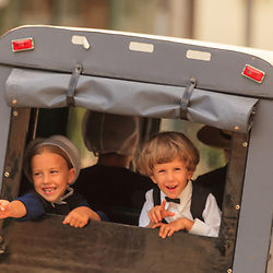 Two young Amish children look out the back of a buggy while traveling on a Lancaster County PA road.