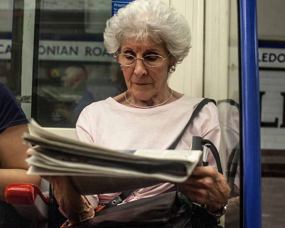 Elderly woman with glasses reading newspaper on the London Underground