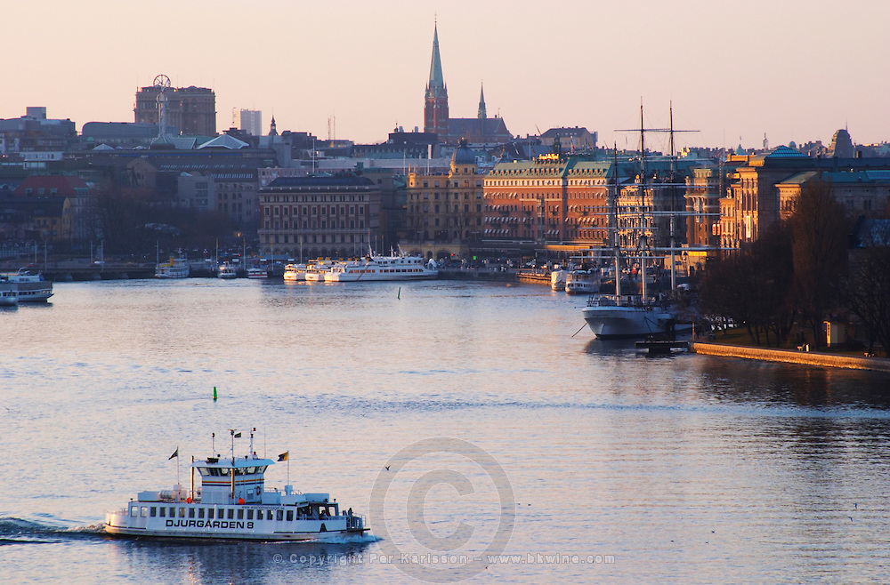 Evening view over Strommen Strom with the Grand Hotel the youth hostel three mast ship af Chapman moored anchored at Skeppsholmen A white old-style passenger ferry boat Djurgarden 8 on the water and white archipelago cruisers on the keyside Stockholm, Sweden, Sverige, Europe