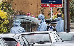 © Licensed to London News Pictures. 18/08/2018. Catford, UK. Investigators in protective suits stand outside a property where a man in his 50's has been stabbed to death in Catford, south London. Police were called at 4am, the victim was pronounced dead at the scene at 5.28am. No arrests have been made. Photo credit: Peter Macdiarmid/LNP