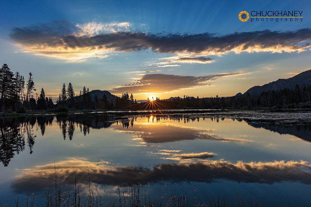 Sunrise clouds reflect into Sprague Lake in Rocky Mountain National Park, Colorado, USA