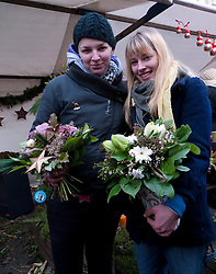 Two young women selling flowers at weekend Kollwitzplatz market in bohemian Prenzlauer Berg in Berlin