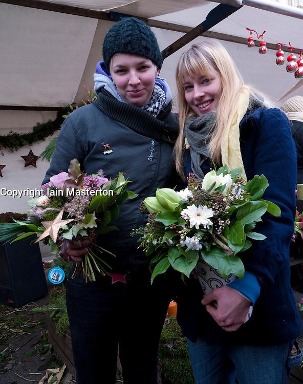 Two young women selling flowers at weekend Kollwitzplatz market in bohemian Prenzlauer Berg in Berlin