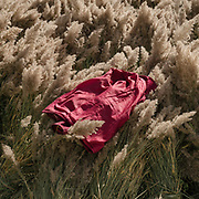 A pink jacket lays on top of hay.  The traditional life of the Wakhi people, in the Wakhan corridor, amongst the Pamir mountains.
