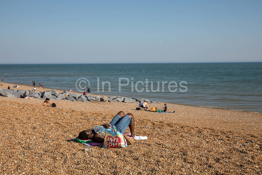 A woman asleep on Hastings beach with a carrier bag that says Awesome on it on the 20th April 2019 in Hastings in the United Kingdom. Hastings is a town on England's southeast coast, its known for the 1066 Battle of Hastings.