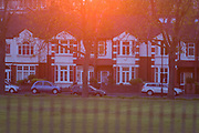 Setting sun turns orange behind Edwardian period homes in south London park. See through a compressed perspective, we see the vertical lines of foreground railings and the houses dating to the beginning of the 20th century, now worth large amounts of money to new buyers. Orange light from the sunset glows from the top of this urban landscape.