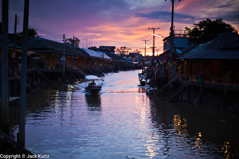 """10 JULY 2011 - AMPHAWA, SAMUT SONGKRAM, THAILAND:   Sunrise on the canal in Amphawa, Thailand, about 90 minutes south of Bangkok. The Thai countryside south of Bangkok is crisscrossed with canals, some large enough to accommodate small commercial boats and small barges, some barely large enough for a small canoe. People who live near the canals use them for everything from domestic water to transportation and fishing. Some, like the canals in Amphawa and nearby Damnoensaduak (also spelled Damnoen Saduak) are also relatively famous for their """"floating markets"""" where vendors set up their canoes and boats as floating shops.     PHOTO BY JACK KURTZ"""