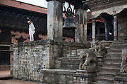Bhaktapur Durbar Square , one of the world heritage sites in Nepal. A man is spinning a top from one of the many temples in the square. Bhaktapur was in the past the capital of Nepal.Summer is rainy season and not many tourists visit Nepal at this time of year.