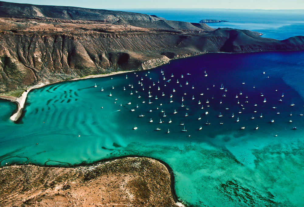 A group of sailboats dot an otherwise pristine lagoon in Baja California.