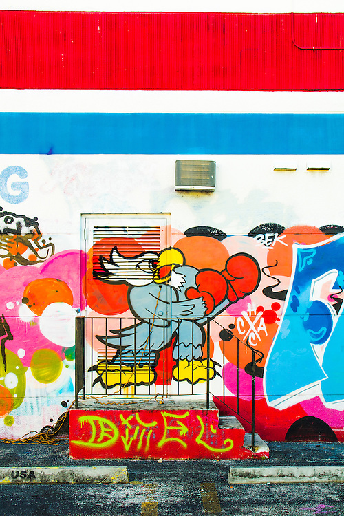 A feisty cartoon bird wears boxing gloves in a mural on a graffiti-bedecked warehouse wall in Miami's Wynwood street art district.
