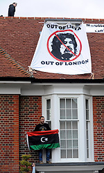 ©London News pictures. 09/03/11. Men on the roof and above the door. A legal notice on the door. Squatters on the roof of a house belonging to the Gaddafi family in Hampstead today. Picture Credit should read Stephen Simpson/LNP