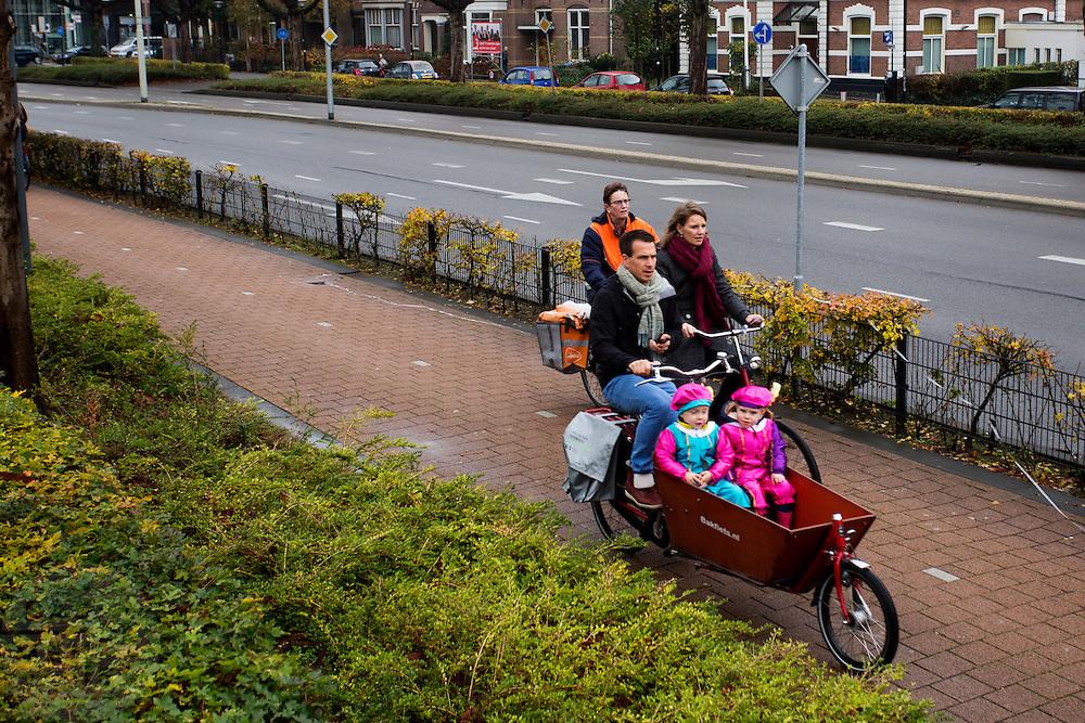 In Amersfoort fietsen ouders met als Pieten verklede kinderen naar de Sinterklaasoptocht.<br /> <br /> In Amersfoort parents cycle with their children dressed as Pete to the Sint Nicholas parade.