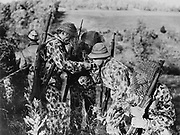 World War II 1939-1945: US Army soldiers in  leopard-spotted camouflage suits with net veiling over helmets and faces, 1942.  Pattern Disruption Weapon Rifle