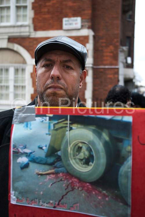 Rida Mohammed (46, and Egyptian / Italian living in London) shows a picture of a protester from Tahrir Square that was killed. He was very keen that this photo was shown to the press. Protesters gather at the Egyptian Embassy in London to demonstrate against President Mubarak and his regime in Egypt. The protest was peaceful and very vocal. Tears were shed at stories told by some of he leading protesters as images of death in the streets of their countrymen were shown.