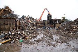 Hydraulic grab machine lifting heavy scrap steel which will be sheared at a metal recycling centre,