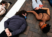 """Erica Joos, left, and Jenelle Figgins comfort each other as they lay on the ground for nine minutes to honor George Floyd during a peaceful protest in Aspen, Colorado. """"Nine minutes is a long time,"""" whispered Figgins. """"I can't breathe,"""" the protesters continued to chant."""