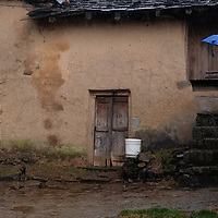 Santa Cruz, California resident Judy Pruzinsky pauses in a village during the rain while hiking in the Himalayan foothills above McLeod Ganj in northern India.<br /> Photo by Shmuel Thaler <br /> shmuel_thaler@yahoo.com www.shmuelthaler.com