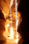 "Three vibrant shafts of light appear in a narrow passage in Antelope Canyon, a slot canyon carved by violent flash floods in Page, Arizona. The beams form only when the sun is nearly overhead, lighting up the blowing sand that fills the canyon, which is dozens of feet deep. The Navajo people call the canyon Tsé bighánílíní dóó Hazdistazí, which means ""the place where water runs through rocks."""