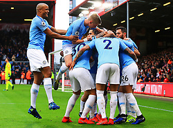 Manchester City's Oleksandr Zinchenko and Vincent Company jump onto team mates as they celebrate with Riyhad Mahrez, after Mahrez scores his sides first goal of the match during the Premier League match at The Vitality Stadium, Bournemouth.
