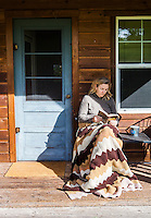 Amy McGuire / A woman reading a book on the porch of The School House Cabin on Browns Farm, Mazama, Washington