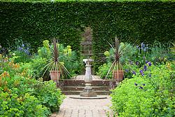 Cordylines in pots around sundial in Mrs Winthrops Garden at Hidcote Manor