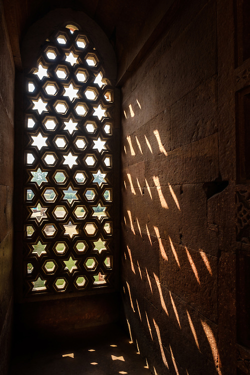 NEW DELHI, INDIA - CIRCA OCTOBER 2016: Intricate carved window in the Alai Darwaza Mosque of the Qutb Minar Complex. The complex features is an array of monuments and buildings at Mehrauli in Delhi, India. An Unesco World Heritage Site and popular touriest attraction in Delhi.