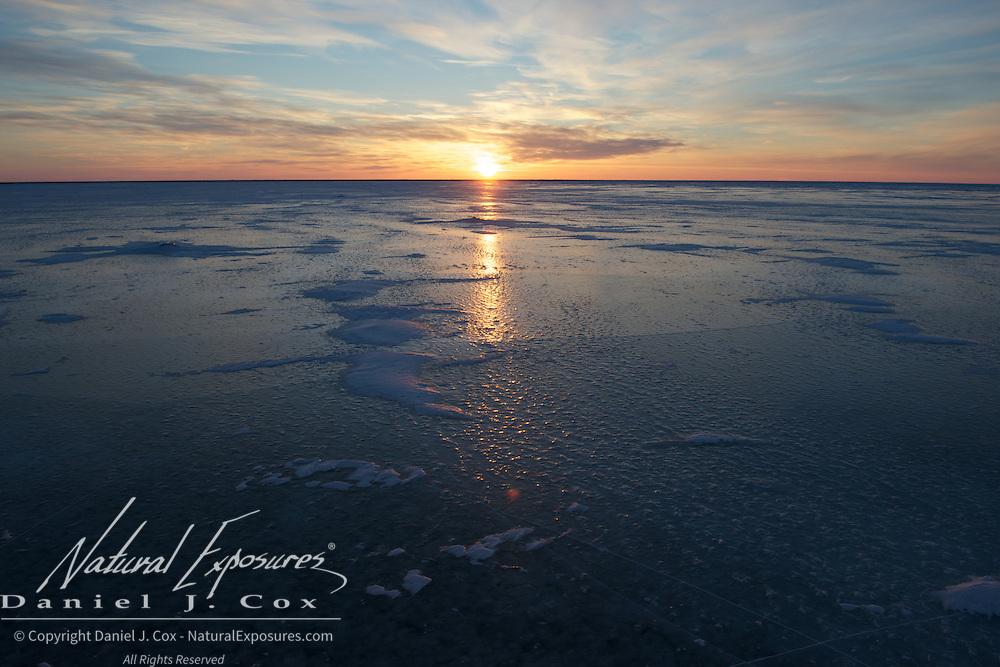 A beautiful sunset baths the blue ice on the lake near Cape Churchill, Manitoba.