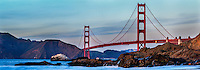 The Golden Gate Bridge as seen from Marshall Beach in San Francisco California on a late Winter day as the waves crash into the surrounding rocks.