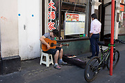 Street scene in Chinatown with a young man playing a guitar outside restaurants in Soho, London, United Kingdom. The present Chinatown is in the Soho area occupying the area in and around Gerrard Street. It contains a number of Chinese restaurants, bakeries, supermarkets, souvenir shops, and other Chinese-run businesses and is in itself a major tourist destination.