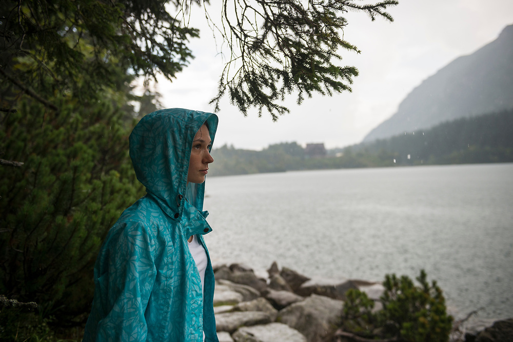 A young Polish woman stops under a tree during a thunderstorm at Morskie Oko, a famous lake in southern Poland. Located within Tatra National Park, Morskie Oko sits at an elevation of about 1400 meters above sea level.