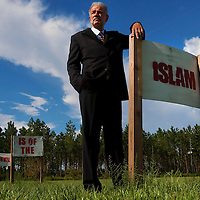 """GAINESVILLE, FL -- August 18, 2010 -- Pastor Terry Jones poses for a portrait with signs that state """"Islam is of the Devil"""" at the Dove World Outreach Center in Gainesville, Fla., on Wednesday, August 18, 2010.  The church is planning on burning multiple copies of the Koran on the anniversary of the September 11th terrorist attacks.  (Chip Litherland for The New York Times)"""