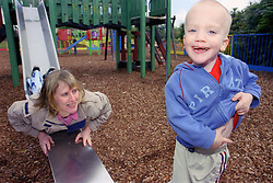 Single mother playing on slide in playground with young son,