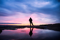 © Licensed to London News Pictures. 02/08/2017. Ilkley UK. A man stands on top of the Cow & Calf rocks at the top of Ilkley Moor in Yorkshire at the break of dawn this morning. Photo credit: Andrew McCaren/LNP