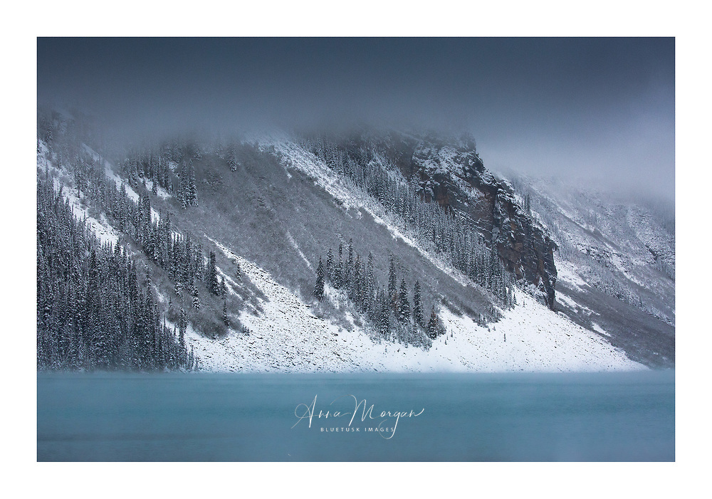 Canadian Rocky Mountains sandwiched between the Intense blue water colour at lake Louise and the dark blue foreboding snowy skies