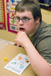 Boy with learning disability sitting at desk in classroom,