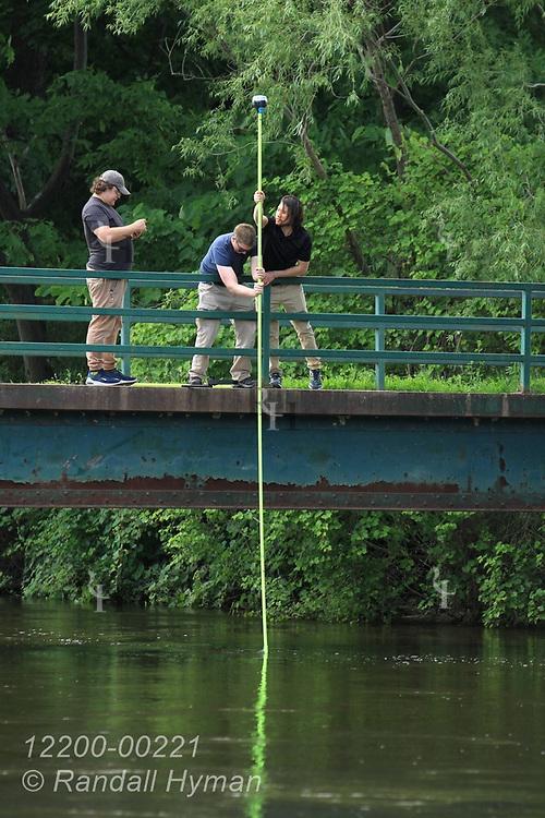 Hyfi CEO Brandon Wong and field tech Matt Craddock feed pole bearing GPS beacon to bottom of flooded Shiawassee River while Nik Krantz records coordinates on cell phone during installation of wireless water-level sensor; Corunna, Michigan.