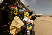 Tchikuteny?s wives in the village In Angola?s Namibe desert, at Giraul, in the Namibe province, Tchikuteny, from the Mucubal tribe, is the leader of a big family, maybe the biggest family in the world.<br /> He is the chief leader, the manager and responsible for the entire village. <br /> In his village, Tchikuteny lives nowadays with most of his big family, his 33 wives, that were once 43, but 10 left the village, and most of their descendants.<br /> Tchikuteny maintains the registry of all the new-borns, totalizing 154 sons, and his grandsons, that are around 60. Nowadays, 4 new babies are on the way, and 3 great grand children were born recently.<br /> Huge harmony, love and respect transpire in the village atmosphere. The sense of a community is the pillar of their sustainability and sustenance and their autonomy depends prominently on cattle and agriculture that is made by the villagers. Nevertheless, Tchikuteny village is in close connection with their surrounding communities. Children attend Giraul School and there is proximity and relations with the extended family that lives in the surroundings.<br /> Being the spiritual leader of the community, Tchikuteny is also responsible for the weekly religious works that happens in the village church. <br /> This big family opened his doors to share with us their daily lives.