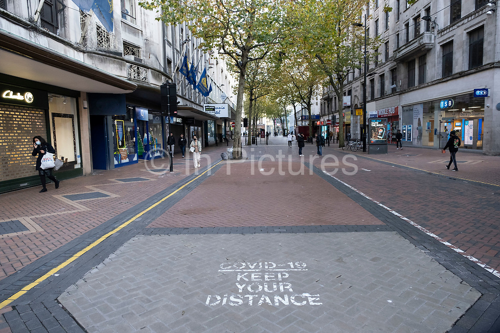 With a fraction of the normal numbers of shoppers around on the day that the second national lockdown came into effect, some people, many of whom are wearing face masks, come to a very quiet New Street in the city centre as all non-essential shops are closed while others remain trading on 5th November 2020 in Birmingham, United Kingdom. The new national lockdown is a huge blow to the economy and for individual businesses who were already struggling with only offering limited services.