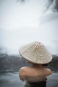 Woman in knit hat bathing in hot spring, Nozawa Onsen, Japan