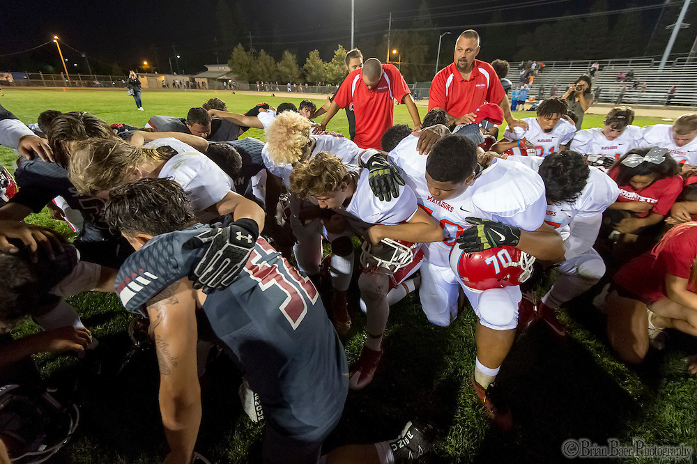 Both teams kneel in prayer after the game as the San Juan Spartans host the Mira Loma Matadors, Friday Sep 16, 2016.<br /> photo by Brian Baer