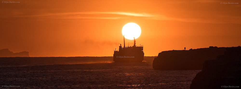 Ferry leaving for Barcelona from Ciutadella in Western Menorca at sunset, Mallorca island can be seen at the far left on the horizon