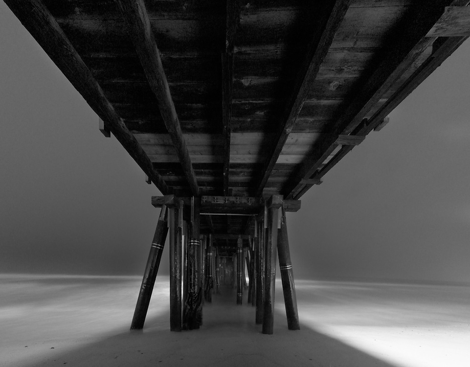 Coastal fog enshrouds the fishing pier at Port Hueneme Beach. Seen in a long exposure panoramic image taken from the sand.