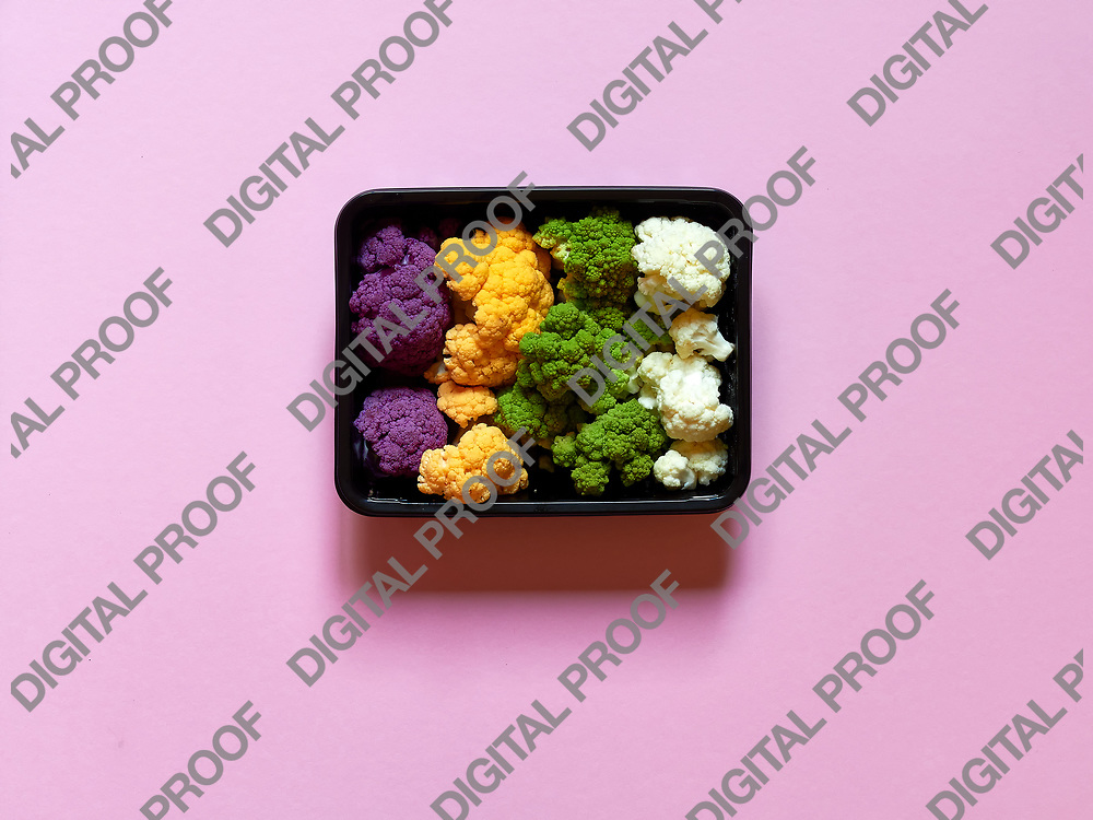 Set of seasonal and colorful cauliflower violet, yellow, green and white boxed in a plastic recipient over a pink background