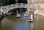 People punting in small boats on the River Cam by the Mathematical Bridge, Cambridge England