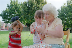 Grandmother teaching grandchildren how to knit,