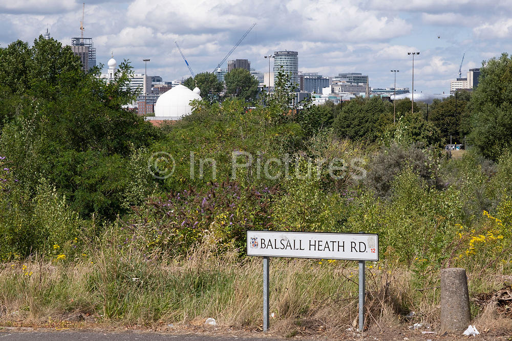 View looking down across overgrown and disused waste ground from Balsall Heath past Birmingham Central Mosque towards the City Centre and the iconic Rotunda building on 3rd August 2020 in Birmingham, United Kingdom. Birmingham is undergoing a massive transformation called the Big City Plan which involves the controversial regeneration of the city centre as well as a secondary zone reaching out further. The Big City Plan is the most ambitious, far-reaching development project being undertaken in the UK. The aim for Birmingham City Council is to create a world-class city centre by planning for the next 20 years of transformation.