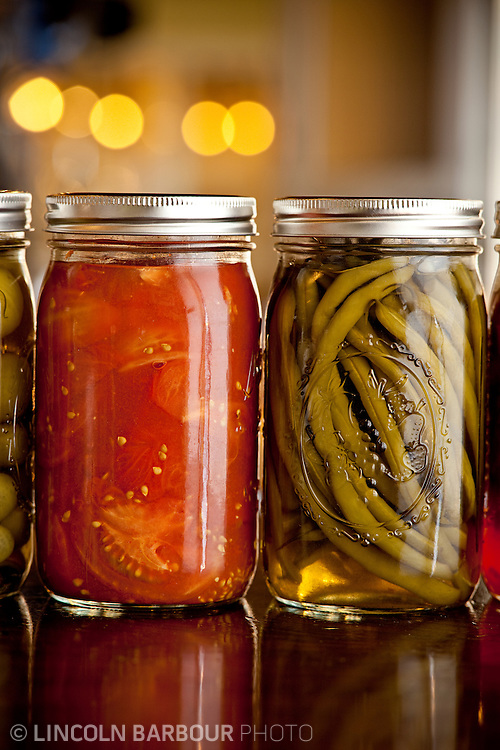 Some pickled tomatoes and green beans inside of mason jars line a counter as decor.