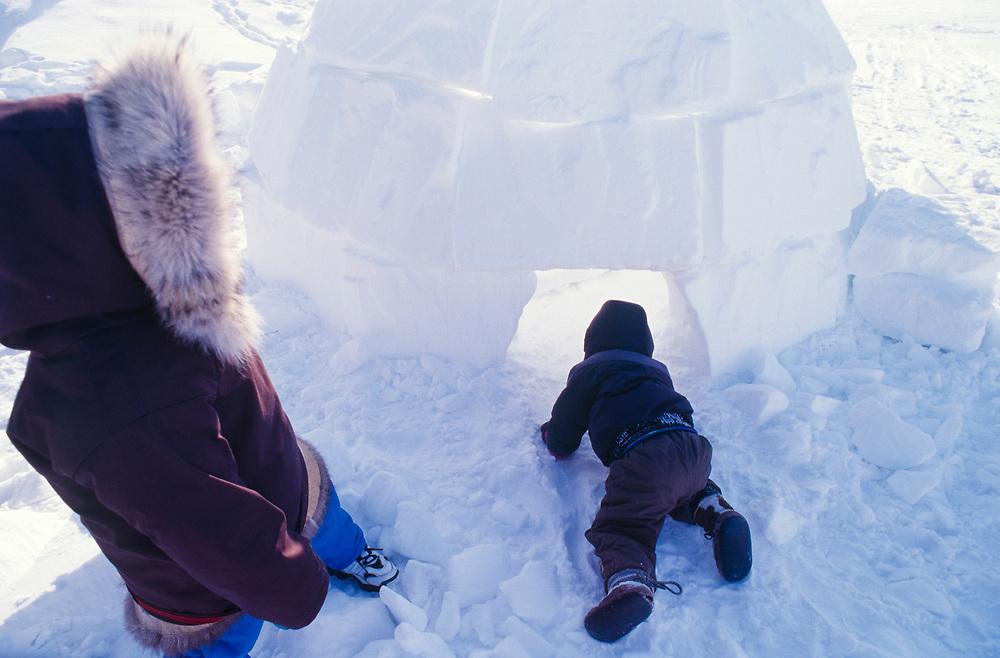 Alaska. Barrow. Two Children playing in an igloo in Barrow.